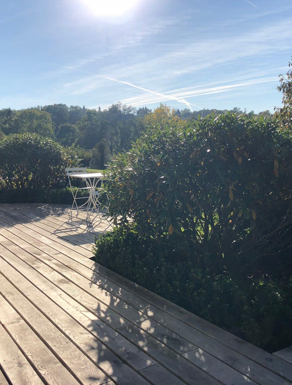 Terrasse avec vue sur le vallon forestier dans le jardin à l'horizon